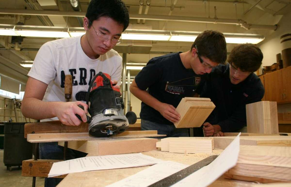 Greenwich High School students Yang Guo prepares to use a router as Anthony Jukic and Woody Waesche work on their projects in the school's