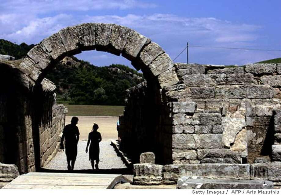 Tourists enter the ancient stadium of Olympia where the Oympic Games were born in 776 B.C., 07 August 2004. Ancient Olympia, about 325 kilometers west of Athens, will be the venue of the 18 August shot put event. AFP Photo/ Aris MESSINIS (Photo credit should read ARIS MESSINIS/AFP/Getty Images) Photo: ARIS MESSINIS