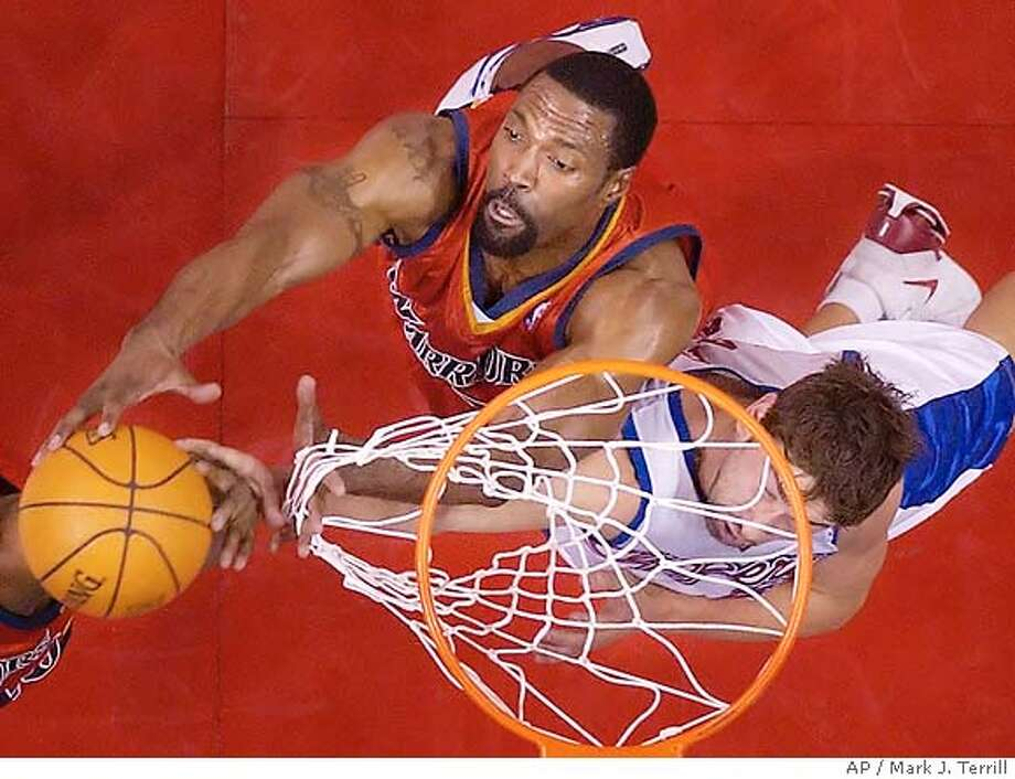 Golden State Warriors' gets his hand caught in the net as he goes after a rebound along with Los Angeles Clippers' Marko Jaric of Serbin-Montenegro during the second half, Saturday, Jan. 29, 2005, in Los Angeles. (AP Photo/Mark J. Terrill) Photo: MARK J. TERRILL
