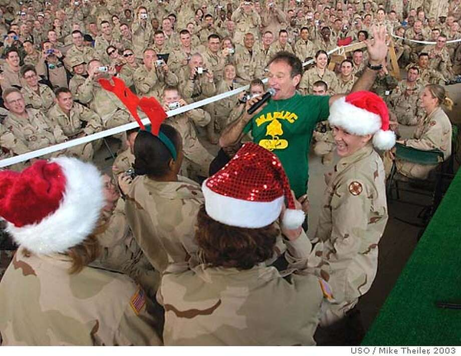 Comedian Robin Williams jokes with U.S. troops dressed in Santa Claus hats at a military base, Wednesday, Dec. 17, 2003 in Balad, Iraq. Williams is touring with a United Service Organizations (USO) holiday tour to entertain American forces in the region. (AP Photo/USO, Mike Theiler) Robin Williams kids around with soldiers at a base in Balad, Iraq, during his USO tour. He said the mood in Iraq was good. Ran on: 02-09-2005  Robin Williams on a USO tour before Christmas in 2003. Photo: MIKE THEILER