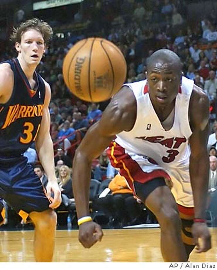 Miami Heat's Dwyane Wade (3) goes after a lose ball as Golden State Warriors' Mike Dunleavy, left, watches in the second quarter Monday, Feb. 7, 2005 in Miami. Miami won 105-96. (AP Photo/Alan Diaz) Photo: ALAN DAZ