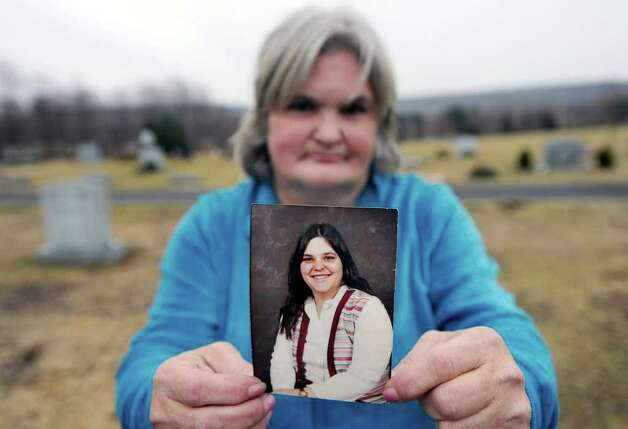 Susan Centmehaiey of Wallingford,, holds a photo of her sister, Mary Harrison, at her sister's gravesite, in the Northford Cemetery, North Branford, Conn., Thursday, Jan. 26, 2011.  Mary Harrison, a Greenwich native, was found murdered on Oct. 30, 1981, in the Town of Hinsdale, N.H. Photo: Bob Luckey / Greenwich Time