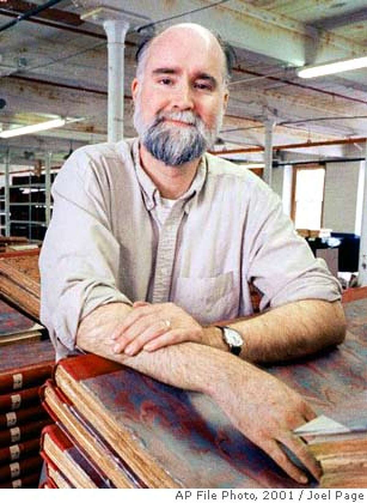 """**FILE**Author Nicholson Baker poses among bound volumes of old newspapers at an old mill building in Rollingsford, N.H., March 3, 2001. Baker organized the nonprofit American Newspaper Repository and become caretaker for the collection. His latest book is """"Checkpoint."""" (AP Photo/Joel Page)"""