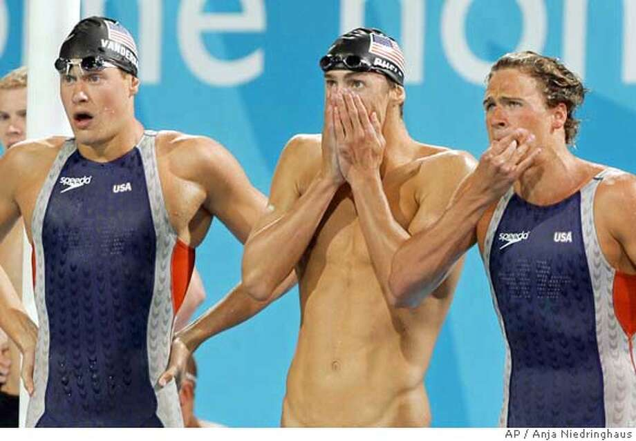 Peter Vanderkaay, left, Michael Phelps, center, and Ryan Lochte, right, look on as Klete Keller swims the final leg of the 4 x 200-meter freestyle relay to win the gold medal at the Olympic Aquatic Centre during the 2004 Olympic Games in Athens, Tuesday, Aug. 17, 2004. (AP Photo/Anja Niedringhaus) Photo: ANJA NIEDRINGHAUS