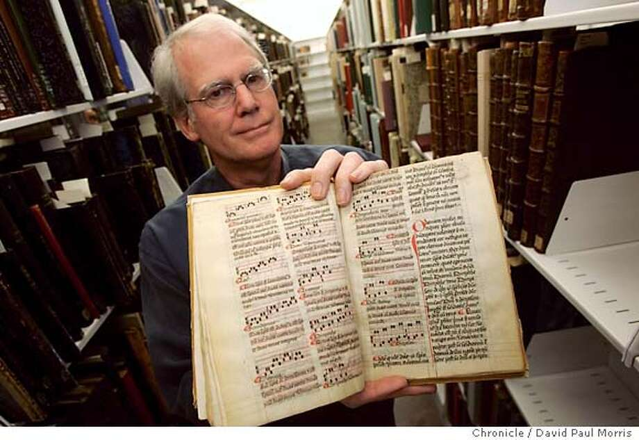 BERKELEY, CA - AUGUST 16: Head Music Librarian John Roberts holds up a 14th century music theory treatise in the new Hargrove Music Library located on the UC Berkeley campus on Monday August 16, 2004. The new Hargrove Music Library opened on the UC Berkeley campus this past July and will house some of the most rare music manuscripts, recordings as well as state of the art learning facilities. (Photo by David Paul Morris/The Chronicle)