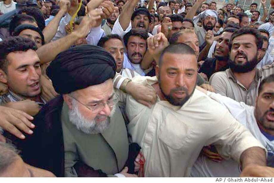 Hussein al-Sadr the head of a delegation of members of the Iraqi National Conference, walks towards the Shrine of Imam Ali to meet with clerics loyal to the radical Shiite cleric Muqtada al-Sadr, as crowds chant is support of Muqtada, in Najaf, Iraq, Tuesday Aug. 17, 2004 ( AP Photo/Ghaith Abdul-Ahad, Pool) POOL Photo: GHAITH ABDUL AHAD