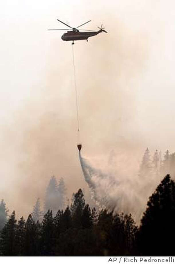 A helicopter drops a load of water on part of the French Fire near French Gulch, Calif., Monday, Aug. 16, 2004. (AP Photo/Rich Pedroncelli) Photo: RICH PEDRONCELLI