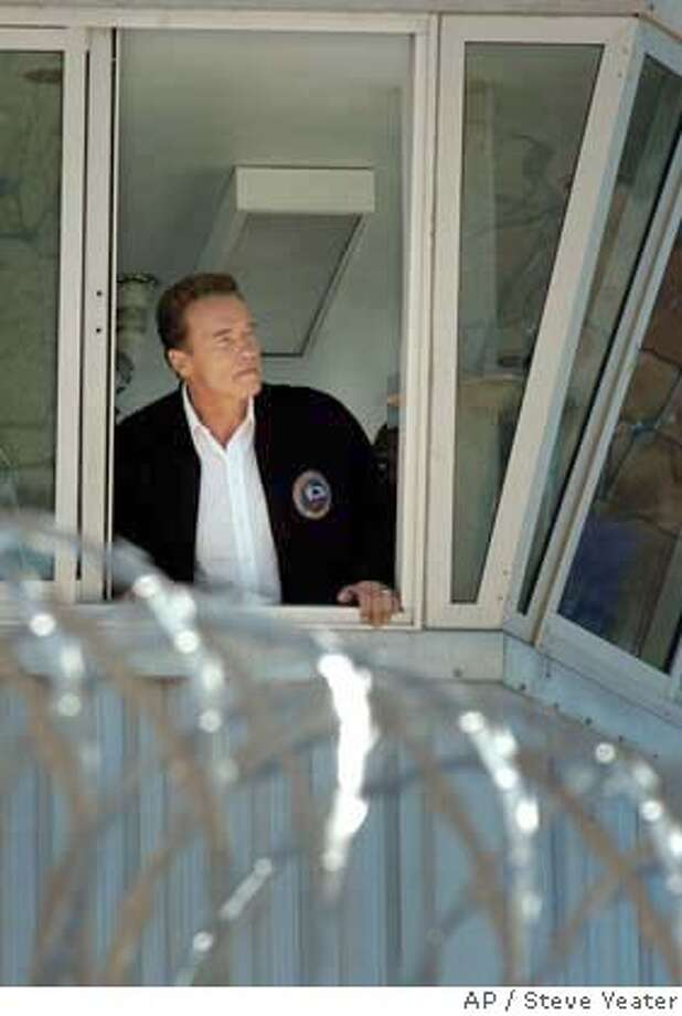 California Gov. Arnold Schwarzenegger looks out from a gun tower over a courtyard at Mule Creek State Prison in Ione, Calif., Monday, Aug. 16, 2004. The governor toured the prison followed by a news conference where he called for intensified efforts to reform the state's prison system.(AP Photo/Steve Yeater) Photo: STEVE YEATER