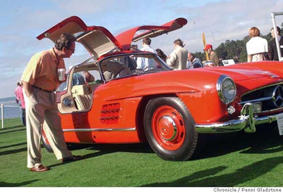 Tom Bau of Laguna Niguel cks out this 1957 Mercedes-Benz 300 SL from Austin, TX. Bau owns a 1956 Gull Wing and a 1961 Roadster.  Concours d'Elegance, display of more than $100 million worth of antique and classic cars on 18th green of Pebble Beach golf course, on the Monterey peninsula. 8/15/04 in Pebble Beach.  Penni Gladstone / The Chronicle Photo: Penni Gladstone
