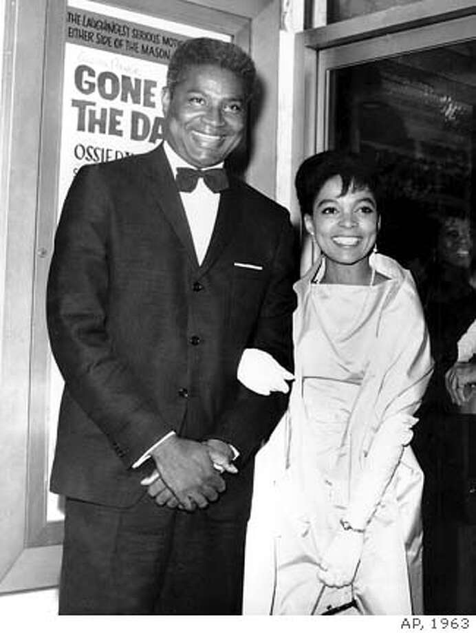 "**FILE**Ossie Davis and wife, Ruby Dee pose in front of their movie poster at the opening night gala of their film ""Gone Are the Days!"" in New York on Sept. 23, 1963. The movie, starring the married couple, is based on Davis's play ""Purlie Victorious."" Davis, the actor distinguished for roles dealing with racial injustice on stage, screen and in real life, has died, an aide said Friday. He was 87. Davis was found dead Friday, Feb. 4, 2005, in his hotel room in Miami, where he was making a film . (AP Photo)"