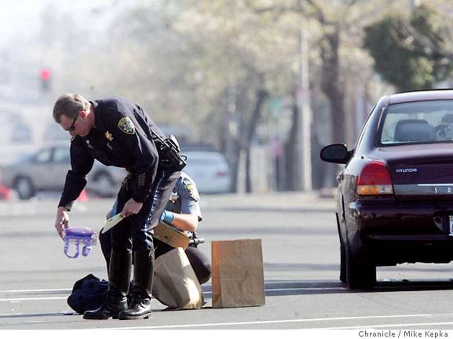 Vallejo PD officer Bill Donavan picks up a lunch box dropped by one the girls hit in Vallejo Thursday morning.  --Two schools were hit in a crosswalk at the intersection of Tennessee and Sutter in Vallejo Thursday morning by a 60-year-old man. At the time this was shot one girl was confirmed dead. 2/3/05  Mike Kepka/The Chronicle Photo: Mike Kepka