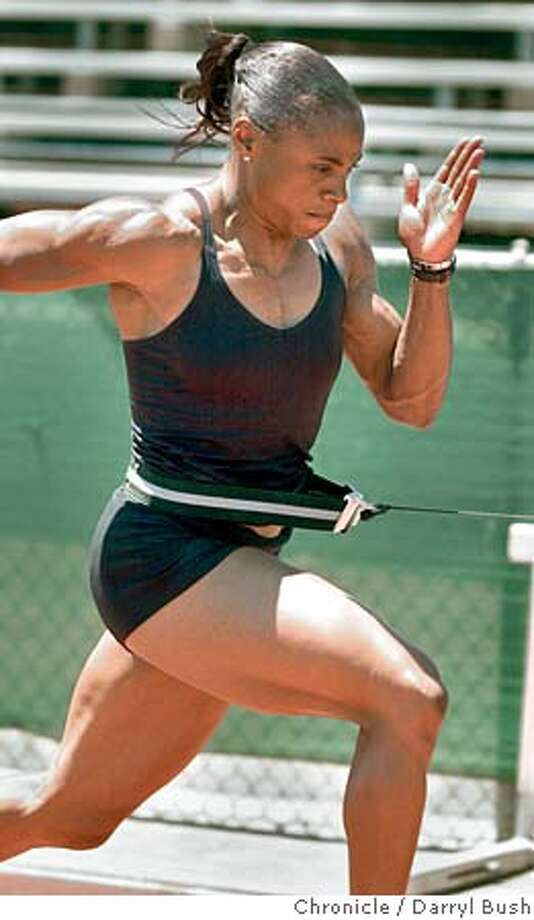 Sprinter Kelli White works out using a belt that pulls her at increased rates of speed, at Lake Chabot College 5/28/03 in Hayward. DARRYL BUSH / The Chronicle Photo: DARRYL BUSH