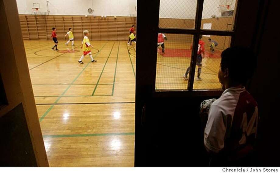 """Jairo Barajas watches practice through the door.The gym at Horace Mann Middle School, long a haven for Mission District kids practicing soccer in the evenings, is closing, due to budget cuts at the Recreation and Park Department. The assistant recreation director who has been staffing the gym in the evenings has been reassigned.  Kids aged 6 to 13 play soccer from 6-8 p.m., adults (women playing in the Golden Gate Women's Recreational Soccer League) take over the gym from 8-9 p.m., Monday through Thursday.  One of the youth teams is """"JC Chivas USA,"""" an under-12 team that plays in the Police Activity League in the city. They will be practicing Thursday night. They are coached by a guy who grew up playing soccer in the same gym.  1/6/05 San Francisco, CA John Storey/The Chronicle Photo: John Storey"""