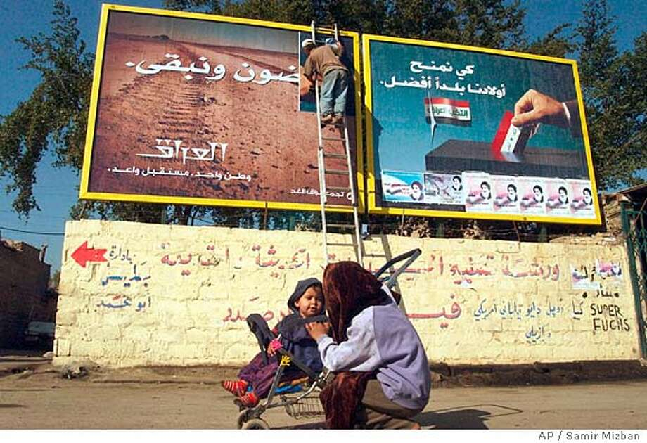 """Billboard posters encouraging citizens to vote in the election, right, are replaced with others stating """"They will leave and we are staying. Iraq - one country, glorious future"""", left, in the Karada area of central Baghdad, Iraq Thursday, Feb. 3, 2005. (AP Photo/Samir Mizban) Photo: SAMIR MIZBAN"""