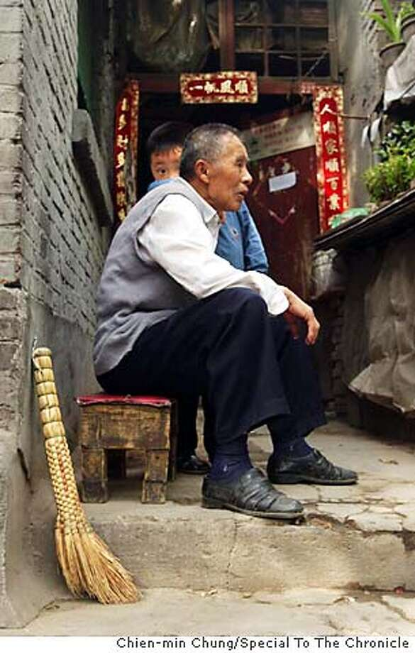 A grandfather and his grandson spend a summer day on their doorstep in the hutongs. Chien-min Chung/Special To The Chronicle Photo: Chien-min Chung