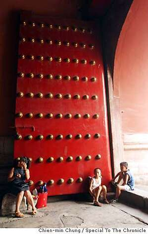 Visitors rest by a door near the Forbidden City. The moat around the Forbidden City was once surrounded by hutongs, but were torn down about 5 years ago. Chien-min Chung/Special To The Chronicle Photo: Chien-min Chung