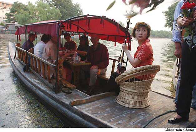 Tourists take a sunset dinner aboard a rowboat in Hohai lake in Beijing. An erhu player, seated in the rear of the boat, serenades the diners with traditional Chinese music during their meal. (photo/Chien-min Chung) Photo: Chien-min Chung