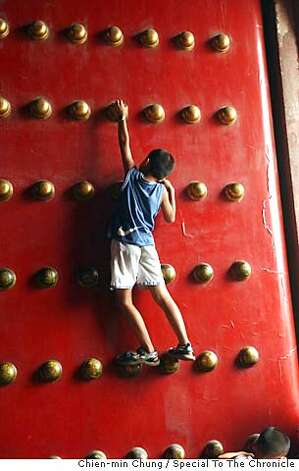 A child climbs a door near the Forbidden City. The moat around the Forbidden City was once surrounded by hutongs, but were torn down about 5 years ago. Chien-min Chung/Special To The Chronicle Photo: Chien-min Chung