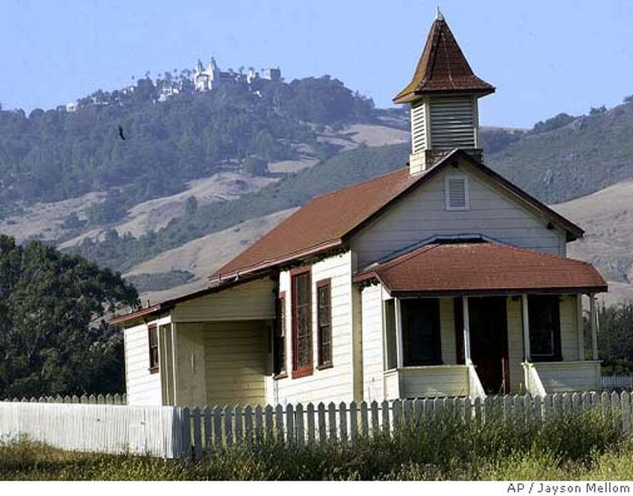 The old schoolhouse in the Old San Simeon Village with Hearst Castle in the background is shown June 3, 2004 near San Simeon, Calif. One of the Hearst Corp.'s biggest selling points for its proposal to spare thousands of acres of Hearst Ranch from development is that its asking price is less than half the land's appraised value. As the preservation plan moves toward approval from state agencies, one of Hearst's old antagonists has emerged to question the land's real worth.(AP Photo/San Luis Obispo Tribune, Jayson Mellom) Photo: JAYSON MELLOM