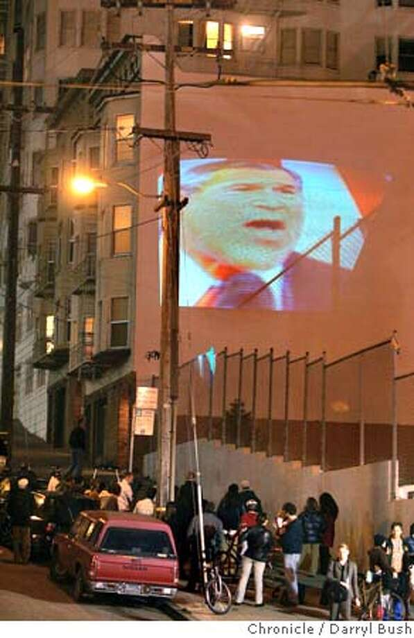 Bystanders watch a live broadcast of the state of the union speech by President George W. Bush projected on a building, by artist Bijan Yashar at Duboce and Market. Event on 2/2/05 in San Francisco.  Darryl Bush / The Chronicle Photo: Darryl Bush