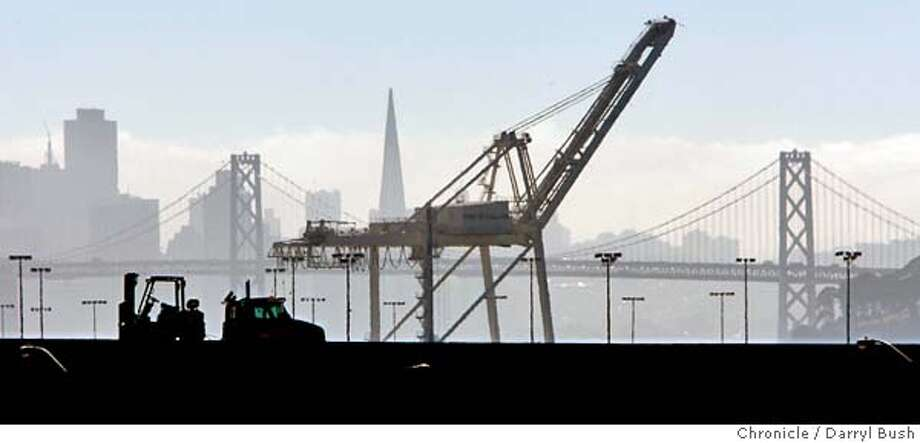 A truck passes by on an overpass with the hazy background of a Port of Oakland crane and the San Francisco skyline in the background. 8/11/04 in Oakland  Darryl Bush / The Chronicle Photo: Darryl Bush