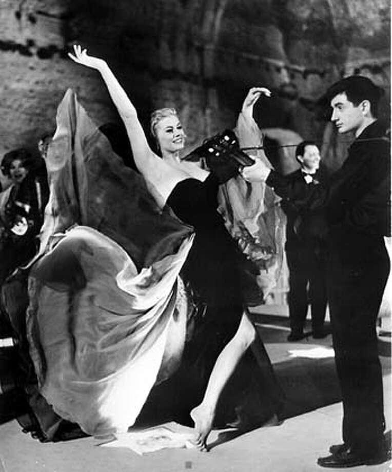 Anita Ekberg, as an American starlet, dances in the streets of Rome in Federico Fellini�s �La Dolce Vita.�
