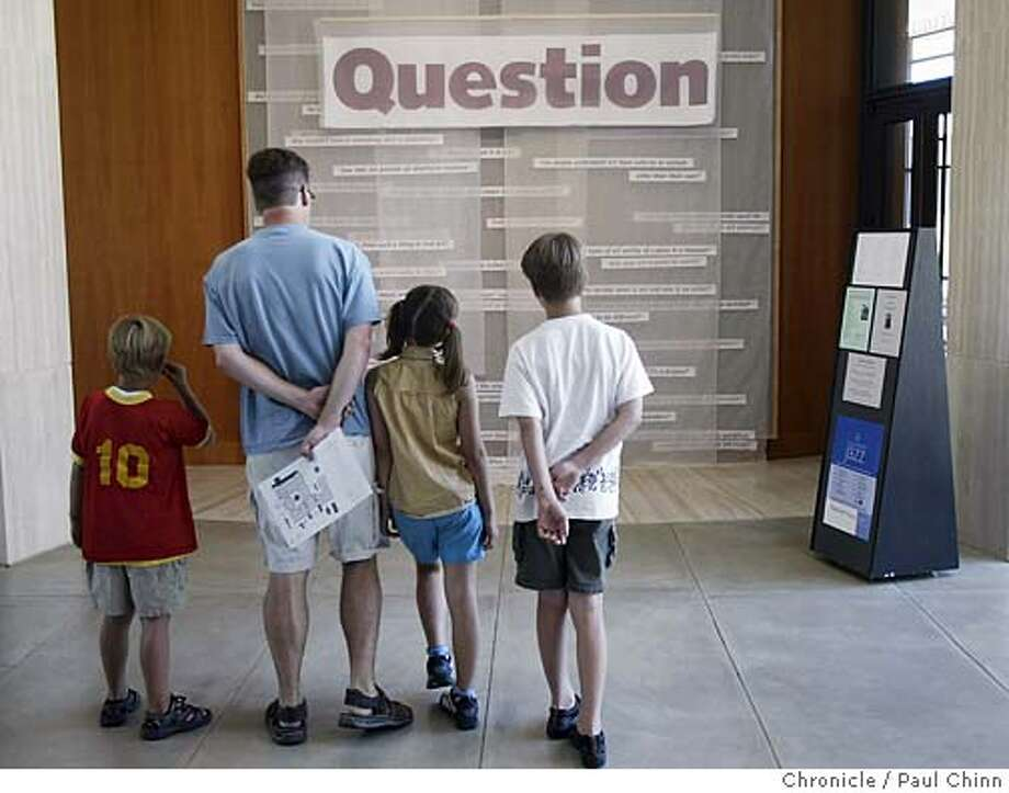 "Visiting from Portland, OR, Paul Buchanan brought his three kids (from left) Theo, Lilah and Myles to see the ""Question"" exhibit. An art exhibit titled ""Question"" asks visitors to interpret what they think art is at the Cantor Arts Center in Stanford on 7/30/04. PAUL CHINN/The Chronicle Photo: PAUL CHINN"