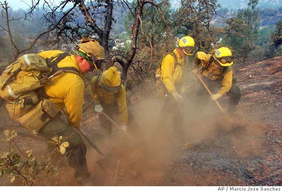 A California Conservation Corps fire crew performs mop up duty on a hillside in Jones Valley, Calif. on Friday, Aug 13, 2004. A wildfire in the Shasta Lake area in Northern California has consumed more than eight thousand acres and destroyed 67 homes. Hundreds of people have been forced to evacuate, and dense smoke fills the skies in the area. (AP Photo/Marcio Jose Sanchez) Photo: MARCIO JOSE SANCHEZ