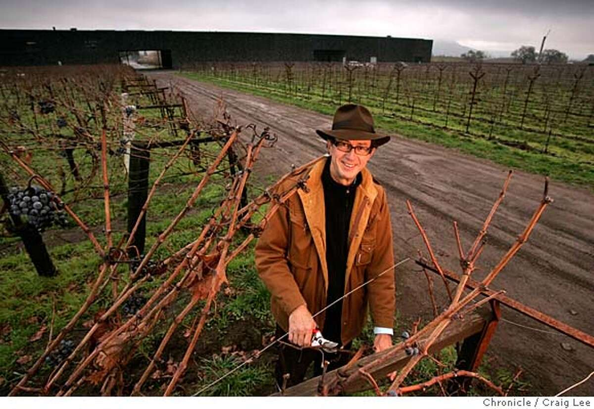 Christian Mouiex, who directs Chateau Petrus in Bordeaux, Dominus in Yountville, Napa Valley and many other brands for his French winemaking family. This photo was taken at Dominus winery in Yountville. Photo of Christian Mouiex in his vineyard with Dominus winery behind in the background. Event on 12/10/04 in Yountville. Craig Lee / The Chronicle