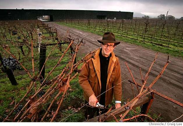Christian Mouiex, who directs Chateau Petrus in Bordeaux, Dominus in Yountville, Napa Valley and many other brands for his French winemaking family. This photo was taken at Dominus winery in Yountville. Photo of Christian Mouiex in his vineyard with Dominus winery behind in the background.  Event on 12/10/04 in Yountville. Craig Lee / The Chronicle Photo: Craig Lee