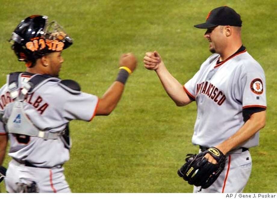 San Francisco Giants starting pitcher Jason Schmidt, right, celebrates his complete game, four-hit, 7-0 win over the Pittsburgh Pirates with Giants's catcher Yorvit Torrealba, Thursday, Aug. 12, 2004, in Pittsburgh.(AP Photo/Gene J. Puskar) Photo: GENE J. PUSKAR