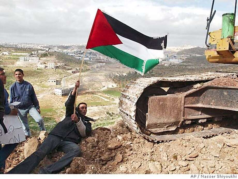 A man with a Palestinian flag lays down in front of a bulldozer, during a demonstration against the confiscation of Palestinian land for the construction of Israel's separation barrier, in the outskirts of the village of Yatta, near the West Bank town of Hebron, Tuesday, Feb. 1, 2005. Israel plans to slow its pullout from five West Bank towns after a day of violence strained an informal cease-fire, Israeli security officials said Tuesday. (AP Photo/Nasser Shiyoukhi) Photo: NASSER SHIYOUKHI