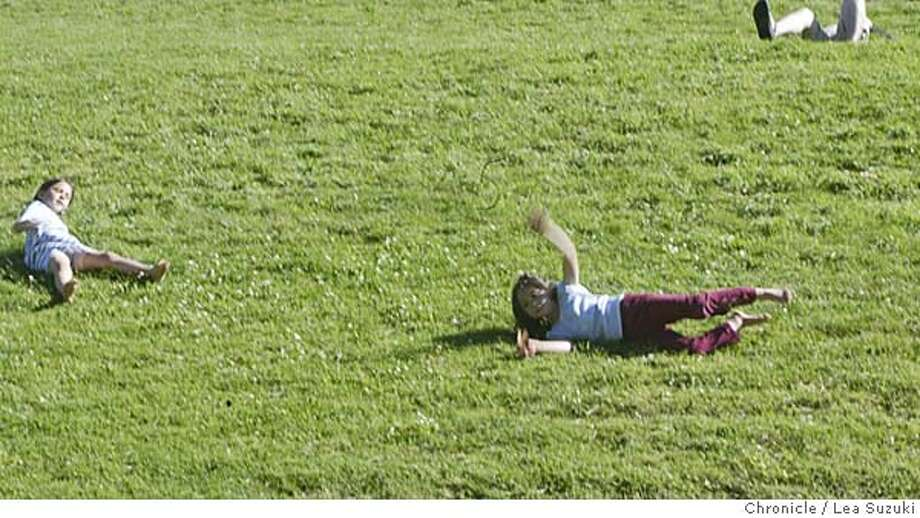 Iris Benson, 6, blue and white striped dress and Ally Lee-Gardner, 6 1/2, blue shirt, enjoy the sunshine in Dolores Park as they roll their bodies down a hill where others took in the sun. Photo taken on 8/11/04 in San Francisco, CA.  Lea Suzuki/ San Francisco Chronicle Photo: Lea Suzuki