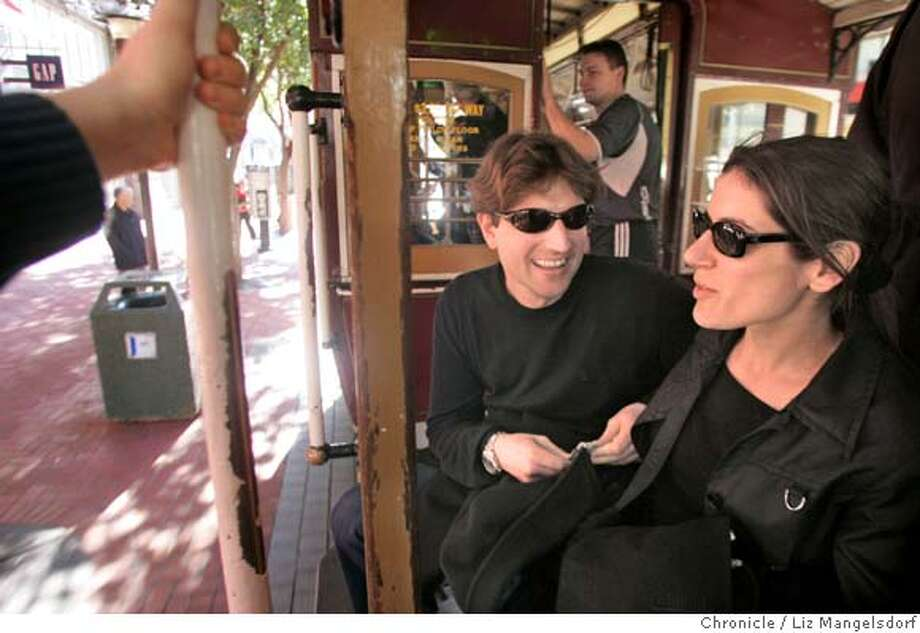 dollar01_018_lm.JPG Event on 1/31/05 in San Francisco.  German tourists, from left G�nter Schmidmeir(cq...please make sure to put the dots over the u) (with dollar in hand to pay the fare) and Constanze Windberg ride the cable car up market street. Story on how EU nations have a great exchange rate right now.  Liz Mangelsdorf / The Chronicle MANDATORY CREDIT FOR PHOTOG AND SF CHRONICLE/ -MAGS OUT Photo: Liz Mangelsdorf