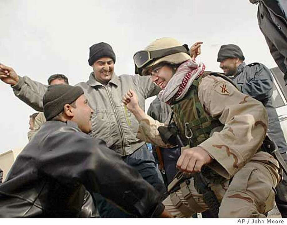 U.S. Army Spc. Luke Saunders dances with Iraqi policemen as they celebrate the arrival of a convoy of ballots from a polling station to a central collection point in Baghdad, Iraq, Monday, Jan. 31, 2005. Iraqi and American forces escorted election officials, ballots and tally sheets to central collection points for tabulation of Sunday's landmark election. Saunders is with the 443rd Civil Affairs Battalion and is from Green Bay, WI.(AP Photo/John Moore) Photo: JOHN MOORE