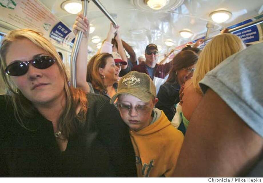 Amber King and Nathan King, 12, both of Santa Rosa squeeze onto the F line trolly near Fisherman's Wharf.  The F line on Muni from Fisherman's wharf to the Ferry building is packed.  MIKE KEPKA/The Chronicle Photo: MIKE KEPKA