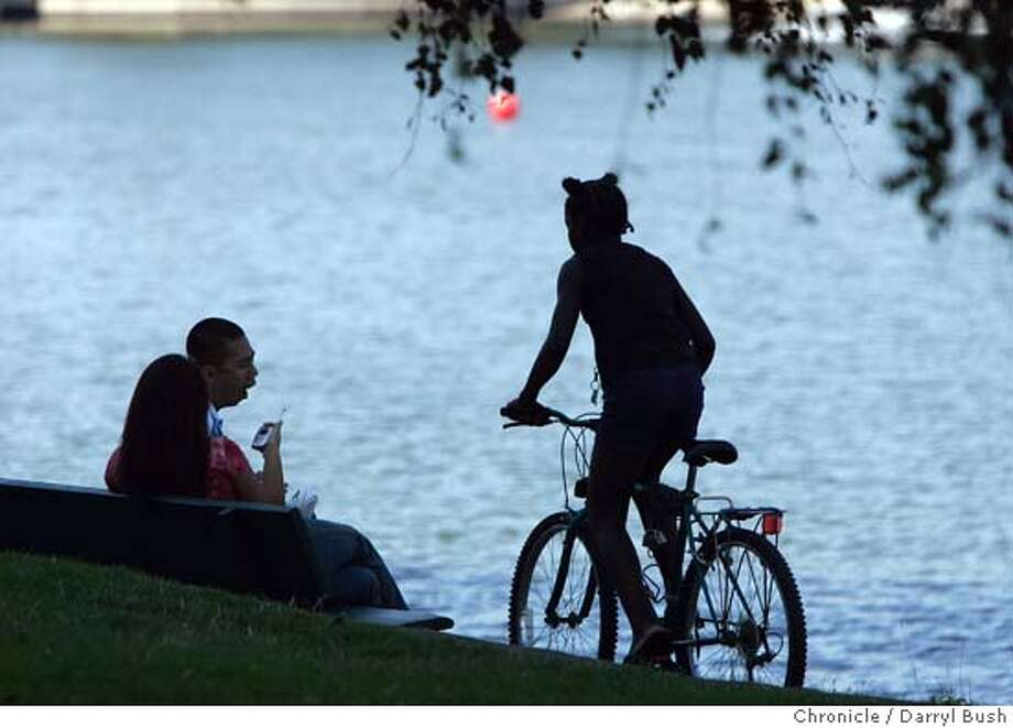 A couple sitting on a park bench watches bicyclists pass by on a lazy summer day by Lake Merritt. 8/11/04 in Oakland  Darryl Bush / The Chronicle Photo: Darryl Bush