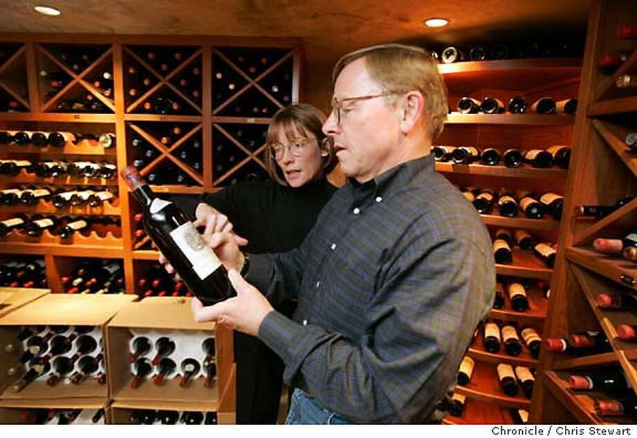 dayinthelife410_cs.jpg  Event on 10/28/04 in San Jose  Cypress Semiconductor CEO and President T.J. Rodgers reads the label a bottle of wine with his wife Valeta in the wine cellar of their Woodside home. A day in the life of T.J. Rodgers, president and ceo of Cypress Semiconductor of San Jose. Chris Stewart / The Chronicle MANDATORY CREDIT FOR PHOTOG AND SF CHRONICLE/ -MAGS OUT Photo: Chris Stewart