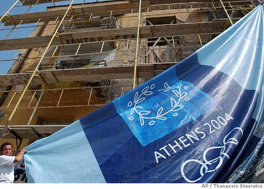 A worker installs a banner with the Athens 2004 logo in front of a building in Athens on Tuesday, Aug. 10, 2004. Dozens of decorative giant banners are being draped over buildings in the city ahead of the Olympics. (AP Photo/Thanassis Stavrakis) Photo: THANASSIS STAVRAKIS