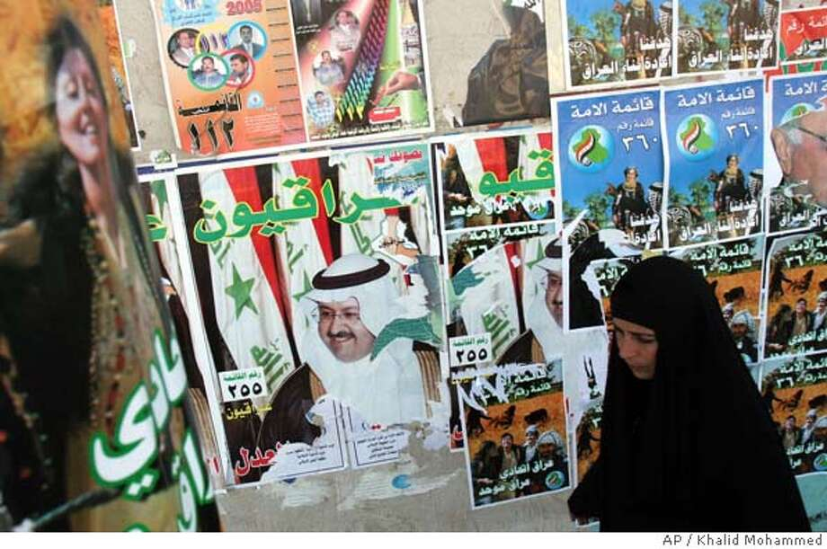 An Iraqi woman walks past a wall covered with elections posters of different parties, in Baghdad, Tuesday, Jan 25, 2005. Iraqis are to choose a 275-member National Assembly and legislatures in each of the 18 provinces in Sunday's balloting. (AP Photo/Khalid Mohammed) Photo: KHALID MOHAMMED
