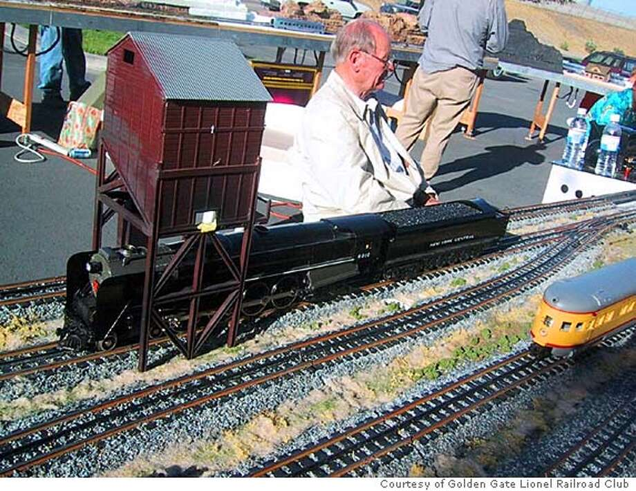 Toy train enthusiast takes in the layout of an O-gauge train display. Photo: Courtesy Golden Gate Lionel Rail
