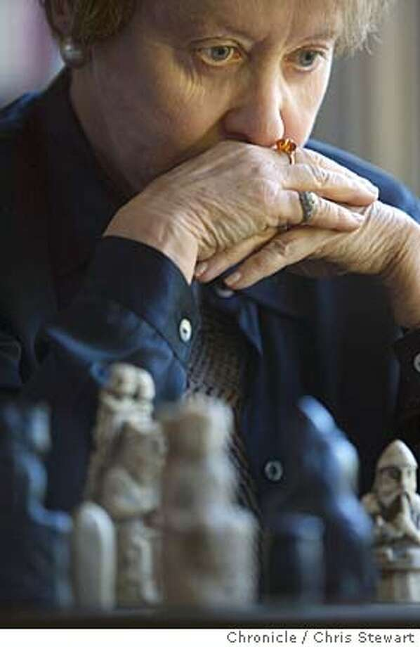 "Event on 7/23/04 in Palo Alto  Stanford lecturer Marilyn Yalom plays chess with the Chronicle's John McMurtrie for a piece that weaves the match into a description of her new book, ""Birth of the Chess Queen."" The book explores the growing role of women in Western society through the game of chess. The chess queen didn't used to exist (the Arab version is still all-male), and its incorporation into the game reflects changing times. Chris Stewart / The Chronicle Photo: Chris Stewart"