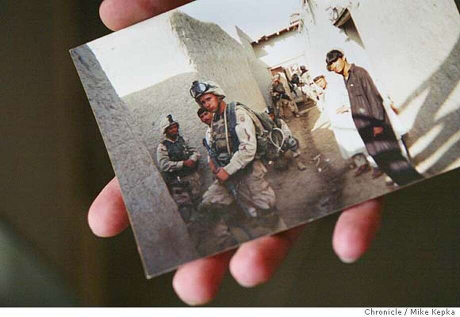 Eric VonEuw (cq) 23, holds a picture from his 8 month tour of duty in Afghanistan in 2002. Eric, who completed his active duty in 2003 is now worried he could be called to serve Iraq during his 3 remaining years as an inactive reservist. - young people who signed up for the military with the idea they would be getting money for college maybe be getting a different deal instead.  MIKE KEPKA/The Chronicle Photo: MIKE KEPKA