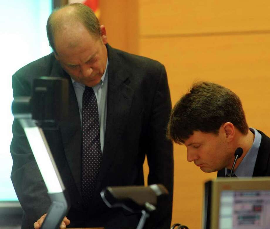Barry Butler, Stand-by Counselor for Sheila Davalloo, shows witness Nelson Sessler a piece of evidence during Davalloo's murder trial before Superior Court Judge Richard Comerford at the Connecticut Superior Court building in Stamford, Conn. Jan. 26, 2012. Davalloo, who allegedly murdered Anna Lisa Raymundo in 2002, is representing herself in the trial. Photo: Lindsay Niegelberg / Stamford Advocate