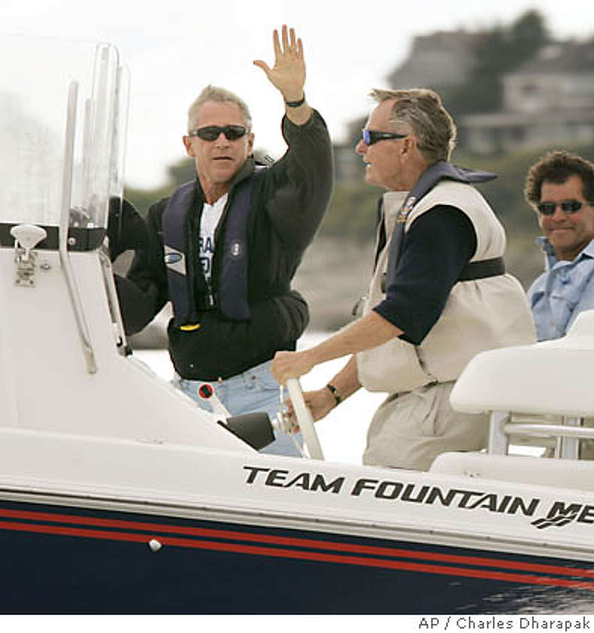 President Bush, left, waves as his father, former President George H.W. Bush, second left, drives their boat while fishing off Kennebunkport, Maine, Friday, Aug. 6, 2004. Others are unidentified. (AP Photo/Charles Dharapak)