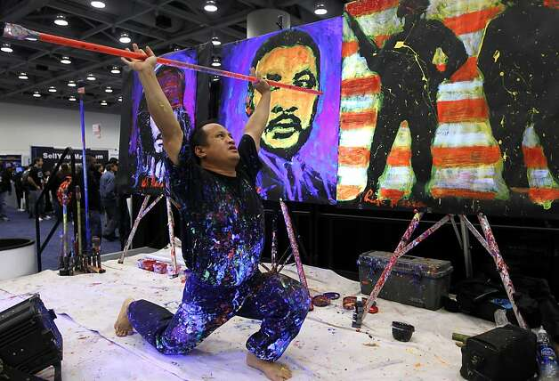 Artist Rick Alonzo stretches while painting portraits at the annual Macworld exhibition in San Francisco, Calif. on Thursday, Jan. 26, 2012. Photo: Paul Chinn, The Chronicle