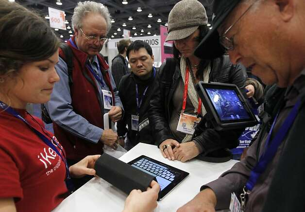 Attendees watch a demonstration of the iKeyboard attachment for the iPad at the annual Macworld exhibition in San Francisco, Calif. on Thursday, Jan. 26, 2012. Photo: Paul Chinn, The Chronicle