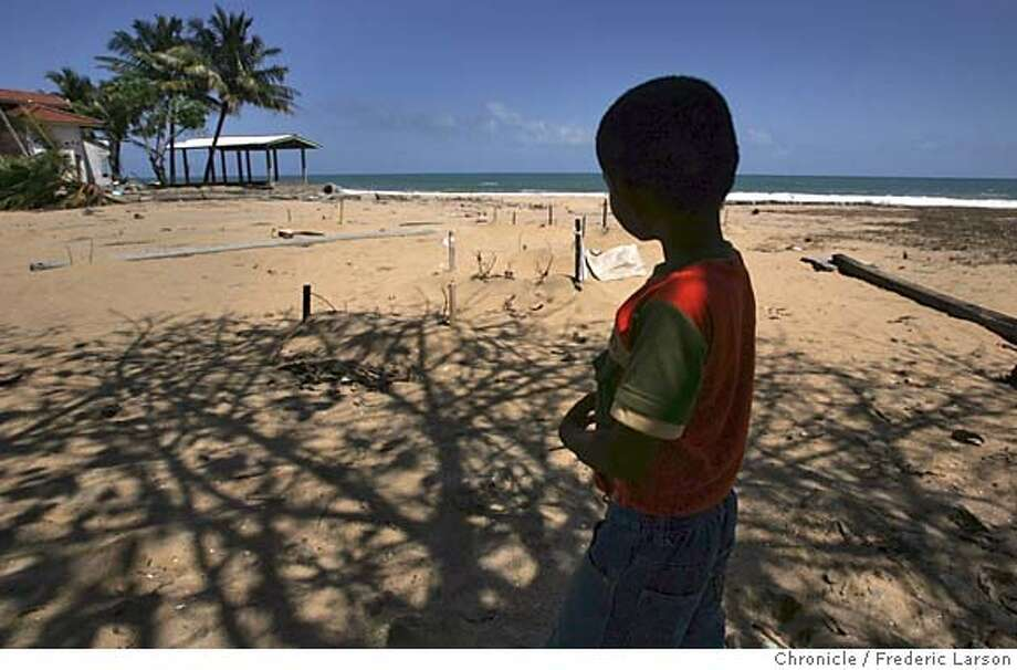 KALMUNAI_F194_fl.jpg Kaushan Ampara (7) pauses at a grave sites (mostly children, 25 victims) which are marked with small white flags meaning death by the Tsunami on the shores of Maligakada, Sri Lanka. The Tsunami that hit southeast Asia December 26th totals over 200K dead, thousands still missing and over two thirds of the shoreline and its immediate vicinity destroyed. Nearly a million are displaced and dispossessed from the tragedy that struck Sri Lanka where local residents are slowly beginning to clear away debris as the county comes to terms with the terrible lost that affected the Sri Lankan coastline. Thousands of Sri Lankan residents mostly front small fishing villages near the ocean front are homeless from the powerful Tsunami the killed over 200K in Southeast Asia 12-26-04. 1/24/05 KALMUNAI Frederic Larson  The San Francisco Chronicle Photo: Frederic Larson