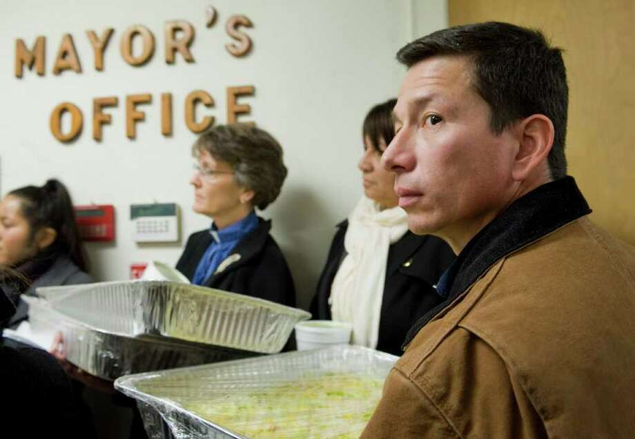 "Ecuadorian Dixon Jimenez, right, delivers tacos to East Haven Mayor Joseph Maturo Jr. in East Haven, Conn., Thursday, Jan. 26, 2012.  Maturo has expressed remorse for saying he ""might have tacos"" to do something for his town's besieged Latino community - but he has no plans to step down. (AP Photo/Jessica Hill) Photo: Jessica Hill, Associated Press / AP2012"