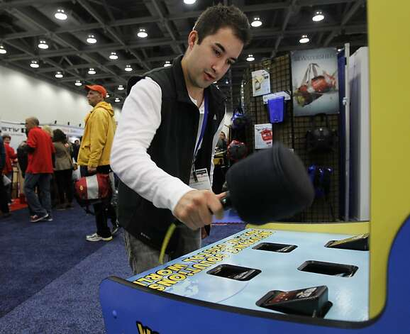 Ramon Soltero plays a game of Whac-a-Phone at the annual Macworld exhibition in San Francisco, Calif. on Thursday, Jan. 26, 2012. Photo: Paul Chinn, The Chronicle